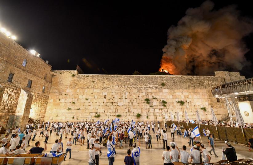 Des Israéliens célèbrent la journée de Jérusalem au Mur occidental alors qu'un incendie est visible en arrière-plan dans l'enceinte de la mosquée al-Aqsa dans la vieille ville de Jérusalem, le 10 mai 2021. (Crédit photo: MENDY HECHTMAN/FLASH90)