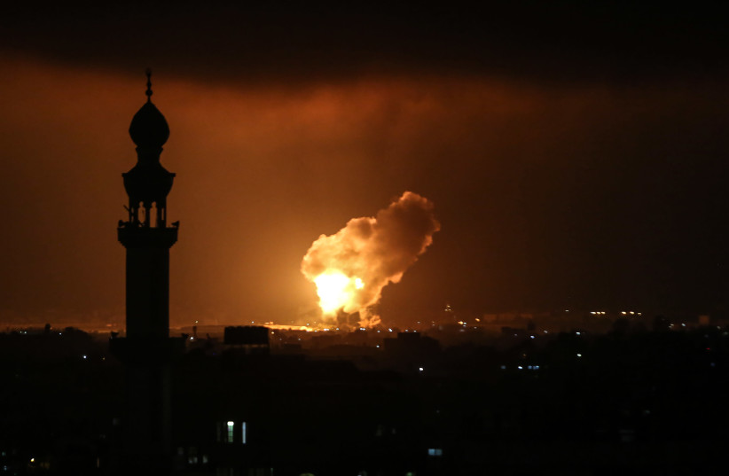 Smoke and flames rise after an Israeli airstrike in a site of the Izz al-Din al-Qassam Brigades, the armed wing of Hamas, in the west of Khan Yunis, in the southern Gaza Strip, on May 11, 2021. (photo credit: ABED RAHIM KHATIB/FLASH90)