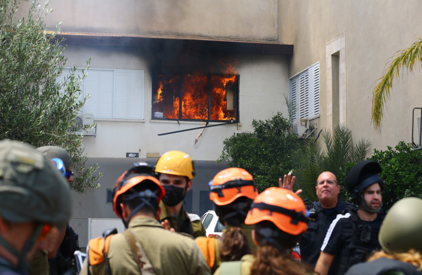 Israeli security forces at the scene where a home was hit by a rocket fired from the Gaza Strip in Ashdod, southern Israel, on May 11, 2021. (photo credit: FLASH90)