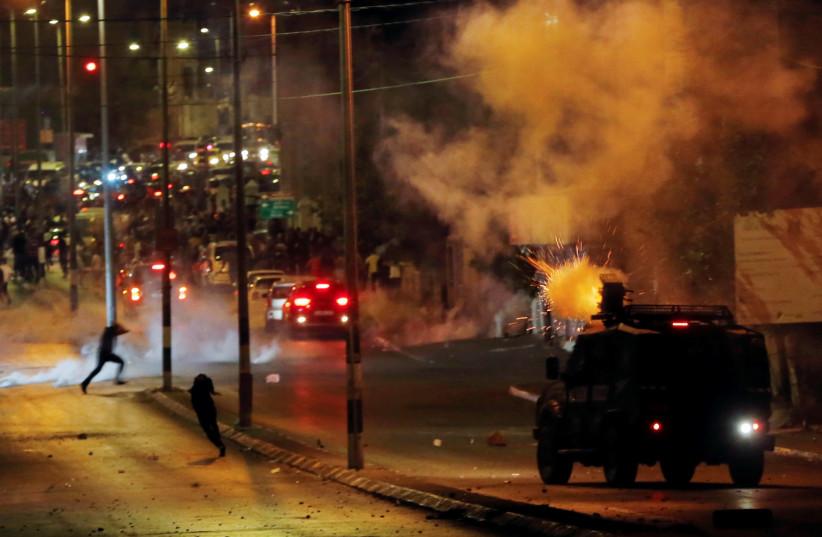 Des Palestiniens courent alors qu'un véhicule militaire israélien tire des bombes lacrymogènes lors d'une manifestation anti-israélienne contre les tensions à Jérusalem, à Bethléem, en Cisjordanie occupée par Israël, le 10 mai 2021 (Crédit photo: MUSSA QAWASMA / REUTERS)