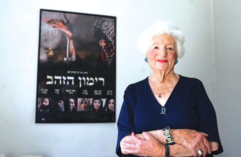Dvora Waysman in front of the poster for the Hebrew film based on her popular book, 'The Pomegranate Pendant' in her Jerusalem apartment. (photo credit: MARC ISRAEL SELLEM)