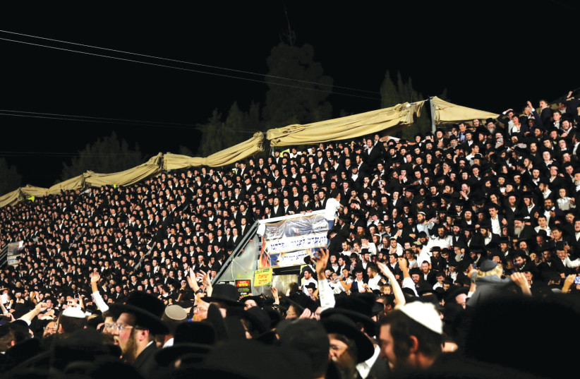 Jewish worshippers sing and dance as they stand on tribunes at the Lag Ba'omer event on Mount Meron on April 29. (photo credit: STRINGER/ REUTERS)