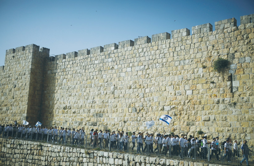 YOUTHS WAVE Israeli flags during the Jerusalem Day march around the Old City walls on Monday.  (photo credit: NIR ELIAS / REUTERS)