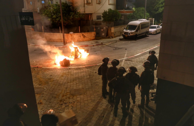 Police seen on the streets of the central Israeli city of Lod, where last night synagogues and cars were torched as well as shops damaged, by Arab residents, May 12, 2021 (photo credit: YOSSI ALONI/FLASH90)