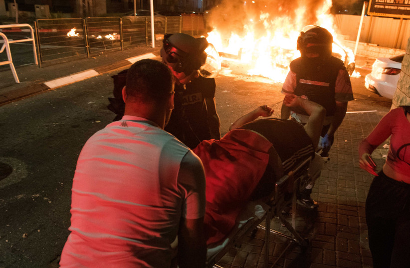 Medics evacuate an injured man during clashes between Arab and Jews in Acre, northern Israel, May 12, 2021.  (photo credit: RONI OFER/FLASH90)