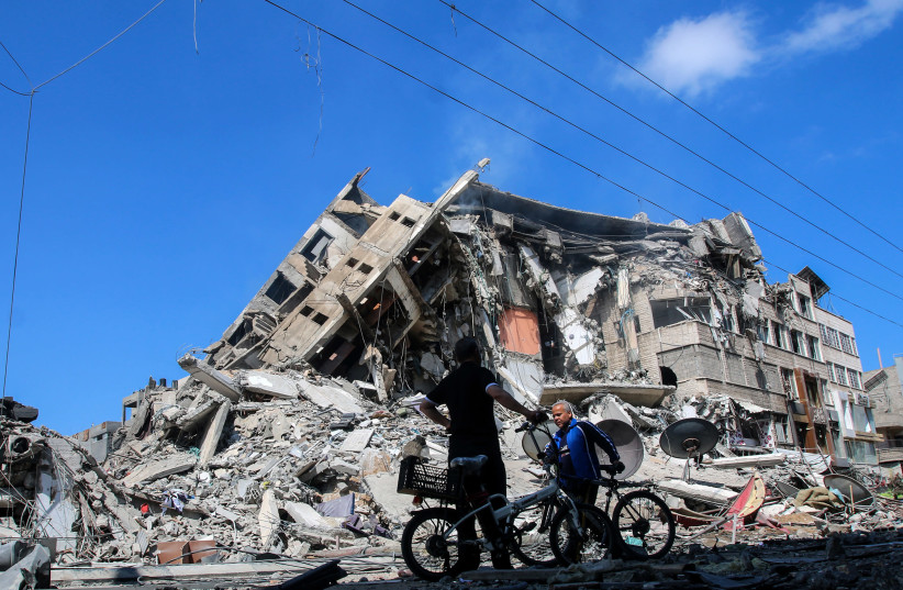 Palestinians are seen checking the damage caused after a 15-floor building was destroyed in an Israeli airstrike in Gaza City, on May 13, 2021. (photo credit: ATIA MOHAMMED/FLASH90)