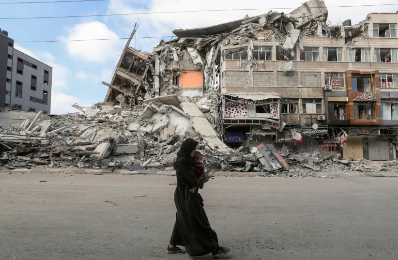 A Palestinian woman carrying her son flees her home during Israeli air and artillery strikes, as she walks near the site of a tower building destroyed in earlier strikes in Gaza City May 14, 2021.  (photo credit: MOHAMMED SALEM/ REUTERS)