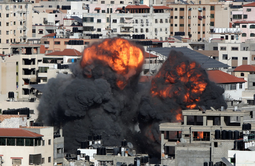 Smoke and flames rise during an Israeli air strike, amid a flare-up of Israeli-Palestinian violence, in Gaza City May 14, 2021.  (photo credit: MOHAMMED SALEM/ REUTERS)