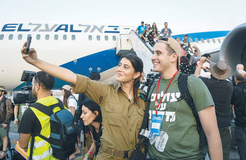 IMMIGRANTS FROM North America arrive at Ben-Gurion Airport on a flight arranged by Nefesh B'Nefesh.  (photo credit: FLASH90)