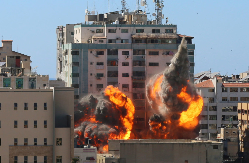 An explosion is seen near a tower housing AP, Al Jazeera offices during Israeli missile strikes in Gaza city, May 15, 2021. (photo credit: ASHRAF ABU AMRAH / REUTERS)
