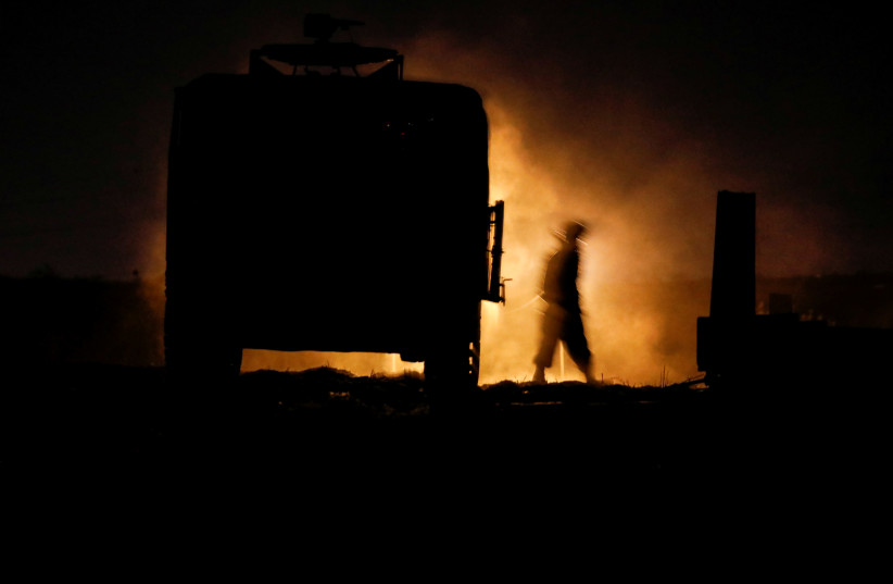 An Israeli soldier walks next to a military vehicle at a mobile artillery unit location on the Israeli side by the Israel border with Gaza (photo credit: BAZ RATNER/REUTERS)
