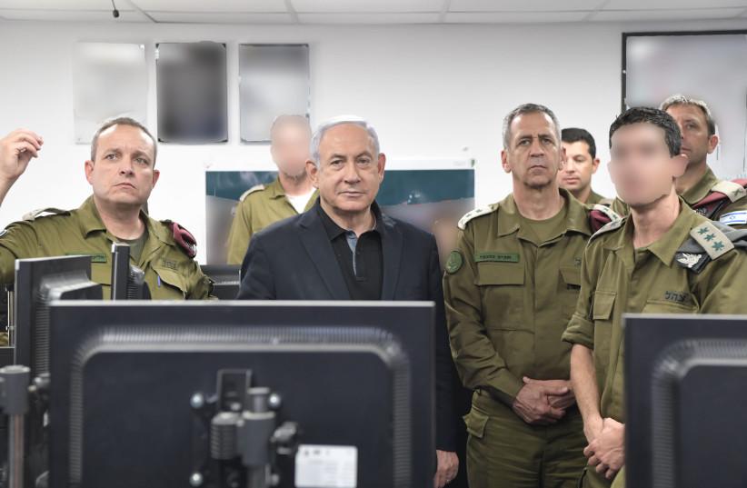 Prime Minister Benjamin Netanyahu stands IDF Chief of Staff Lt.-Gen. Aviv Kochavi in the war room. (photo credit: GPO)