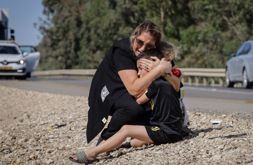 A woman and child take cover as a siren sounds a warning of incoming rockets fired from the Gaza strip in the city of Ashkelon, southern Israel, on May 19, 2021.  (photo credit: OLIVIER FITOUSSI/FLASH90)
