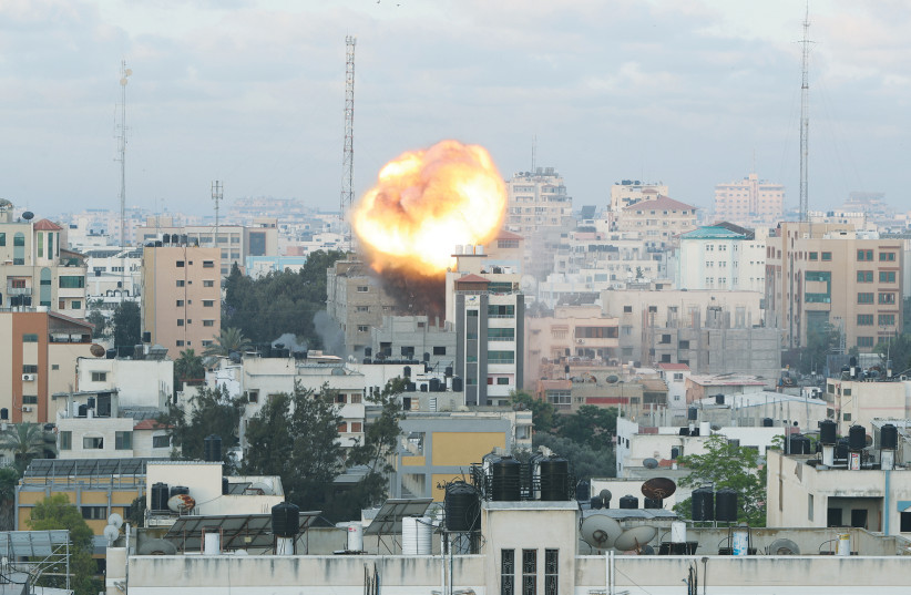 SMOKE AND FLAMES follow an Israeli air strike on a building in Gaza City on Tuesday. (photo credit: MOHAMMED SALEM/REUTERS)