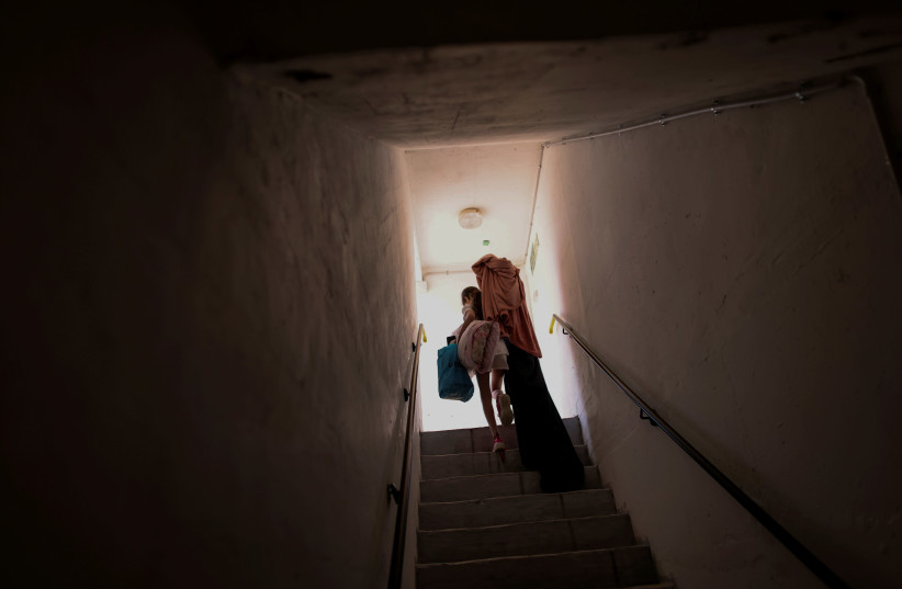 An Israeli girl carries her belongings as she walks out from a public bomb shelter back home, following Israel-Hamas truce, in Ashkelon, Israel May 21, 2021. (photo credit: RONEN ZVULUN/REUTERS)