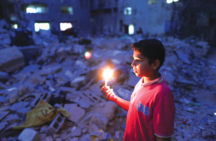 A BOY holds a candle at the site of a house that was destroyed by Israeli airstrikes during the Israeli-Palestinian fighting, in Gaza earlier this week. (photo credit: SUHAIB SALEM/REUTERS)