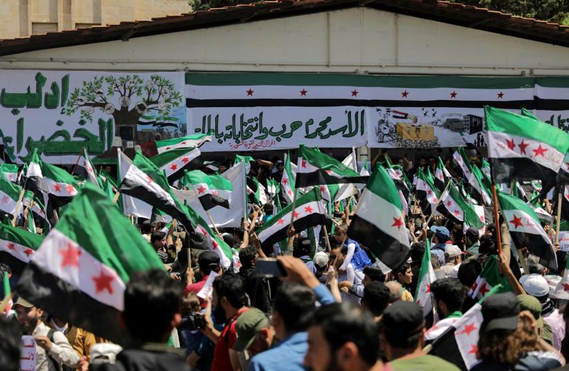 Des gens participent à une manifestation contre le président syrien Bachar al-Assad et aux élections présidentielles, à Idleb, en Syrie, le 26 mai 2021. (Crédit photo : KHALIL ASHAWI / REUTERS)