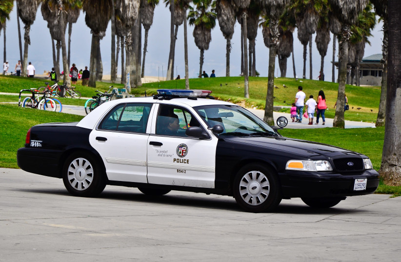 Los Angeles Police Department (LAPD) officers in a car (illustrative). (photo credit: Wikimedia Commons)