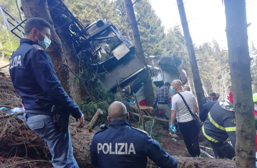 Police and rescue service members are seen near the crashed cable car after it collapsed in Stresa, near Lake Maggiore, Italy May 23, 2021. (photo credit: REUTERS)