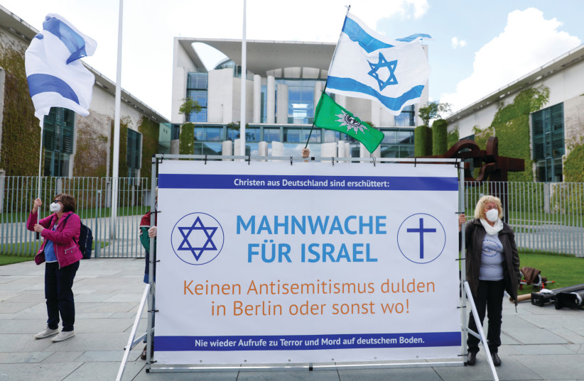 PEOPLE WAVE Israeli flags and display a police Trade Union banner reading 'Solemn vigil for Israel. Don't accept antisemitism in Berlin or elsewhere' outside the Chancellery in Berlin earlier this month. (photo credit: MICHELE TANTUSSI/REUTERS)