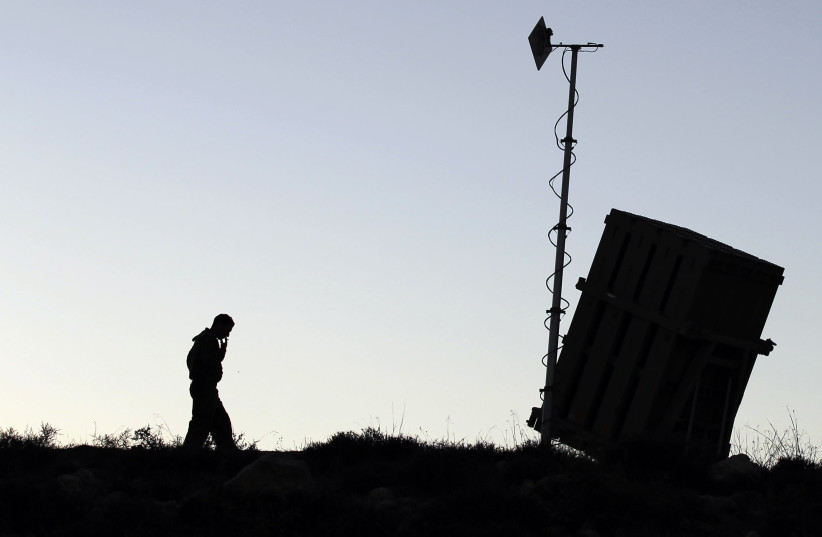 An Israeli soldier walks next to an Iron Dome missile interceptor battery after it is being positioned on the outskirts of Jerusalem, September 8, 2013.  (credit: REUTERS/AMMAR AWAD)