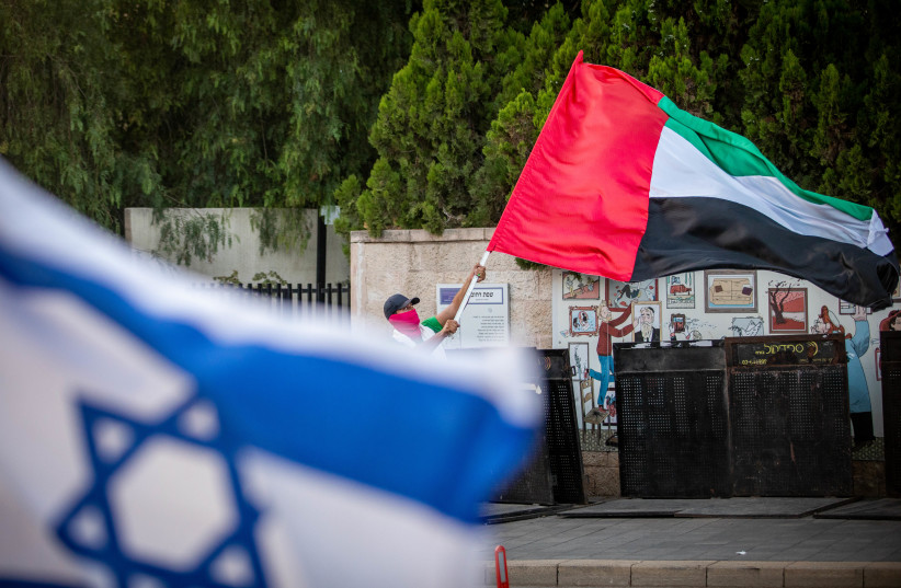 A man waves a giant United Arab Emirates flag outside the Prime Minister's official residence in Jerusalem on August 19, 2020 (photo credit: YONATAN SINDEL/FLASH 90)