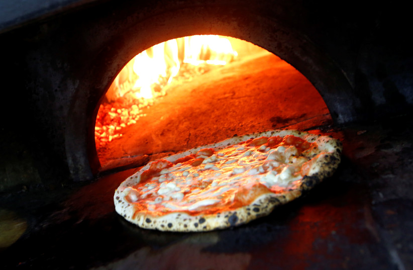 Pizza Margherita is prepared in a wood-fired oven at L'Antica Pizzeria da Michele in Naples, Italy December 6, 2017. (photo credit: REUTERS/CIRO DE LUCA)