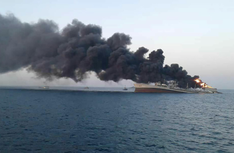 Smoke rises from Iran navy's largest ship in Jask port in the Gulf, Iran, June 2, 2021. (photo credit: WANA (WEST ASIA NEWS AGENCY) VIA REUTERS)