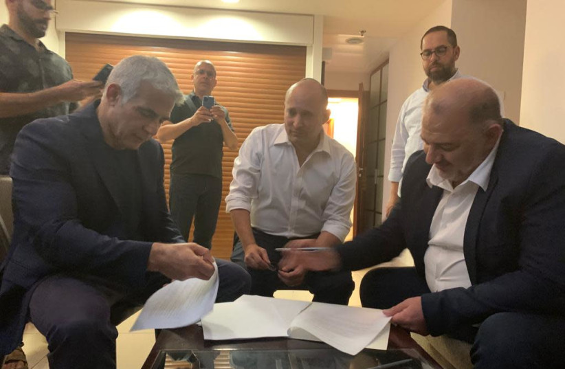 Naftali Bennett, Yair Lapid and Mansour Abbas are seen signing a coalition deal. (photo credit: RA'AM)