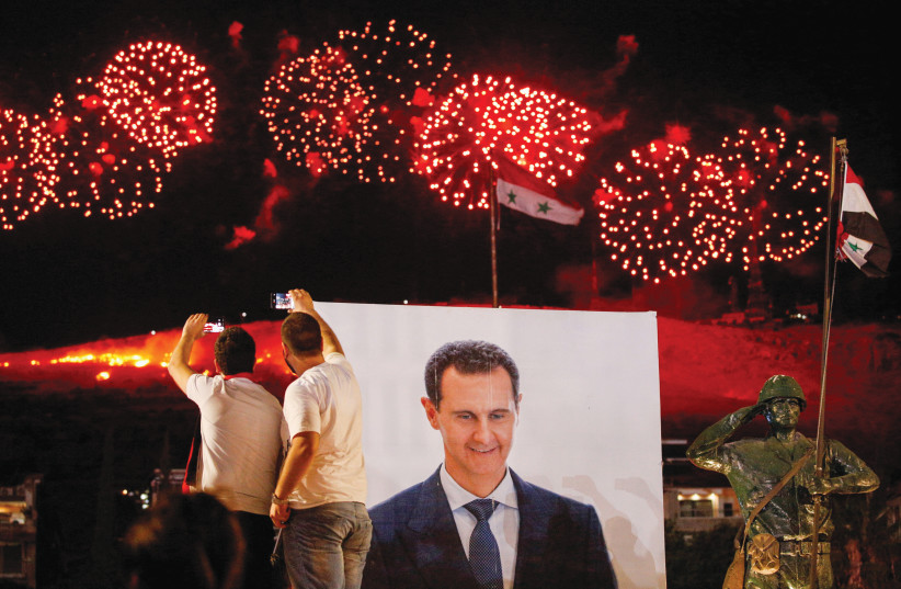SUPPORTERS OF Syrian President Bashar Assad celebrate after he won a fourth term in office, in Damascus on May 27 (photo credit: REUTERS/OMAR SANADIKI)