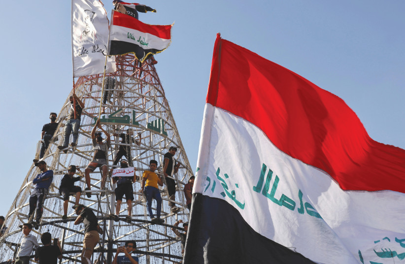 DEMONSTRATORS CLIMB a structure during an anti-government protest in Baghdad, last week. (photo credit: THAIER AL-SUDANI/REUTERS)