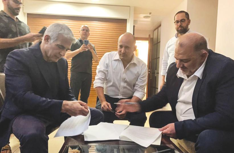 YESH ATID leader Yair Lapid, Yamina head Naftali Bennett and Ra'am leader Mansour Abbas sign coalition agreements at the Kfar Maccabiah hotel Wednesday night.  (photo credit: RA'AM)