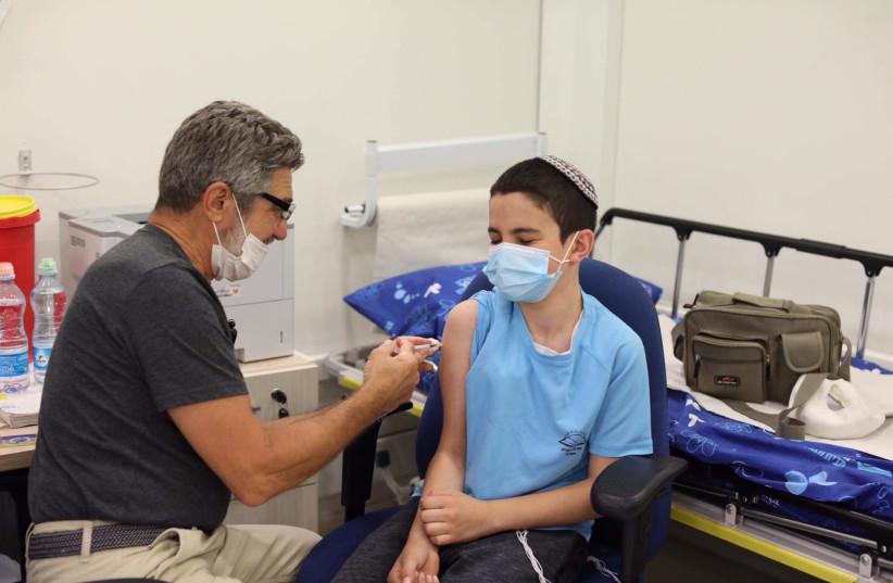 Yossi Guggenheim, 12, getting vaccinated (photo credit: MARC ISRAEL SELLEM)