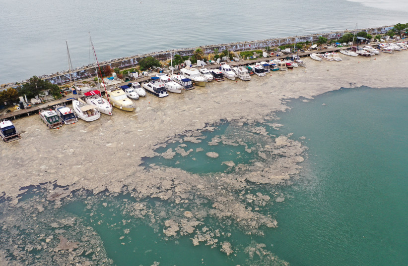 """An aerial view shows a thick layer of """"sea snot,"""" consisting of a wide variety of microorganisms, that covers the sea near the coast in the Bostanci harbor in Istanbul, Turkey May 31, 2021. Picture taken with a drone May 31, 2021.  (photo credit: MEHMET CALISKAN/REUTERS)"""