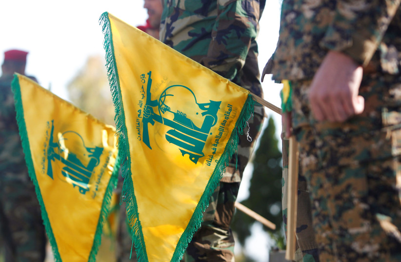 Hezbollah members hold flags marking Resistance and Liberation Day, in Kfar Kila near the border with Israel, southern Lebanon, May 25, 2021 (photo credit: REUTERS/AZIZ TAHER)