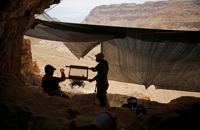 Volunteers with the Israeli Antique Authority work at the Cave of the Skulls, an excavation site in the Judean Desert near the Dead Sea, Israel June 1, 2016. (photo credit: REUTERS/RONEN ZEVULUN)