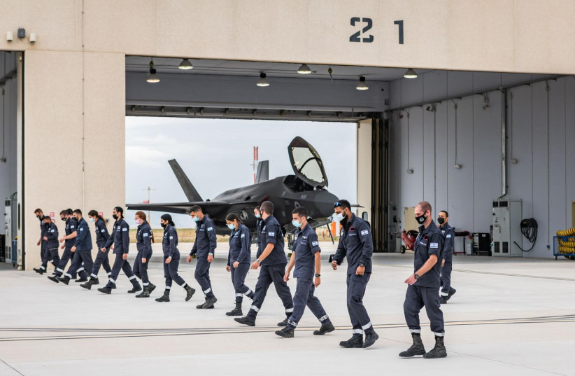 Israeli Air Force (IAF) personnel are seen marching by a fighter jet hanger. (photo credit: IDF SPOKESPERSON'S UNIT)