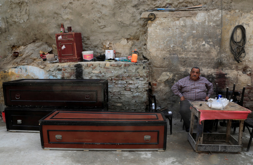 Mohamed Mahmoud, 65 years old a traditional undertaker looks on near lacquered wooden coffins and accessories at a working area in the Shobra district of Cairo, Egypt April 7, 2021.  (photo credit: REUTERS)