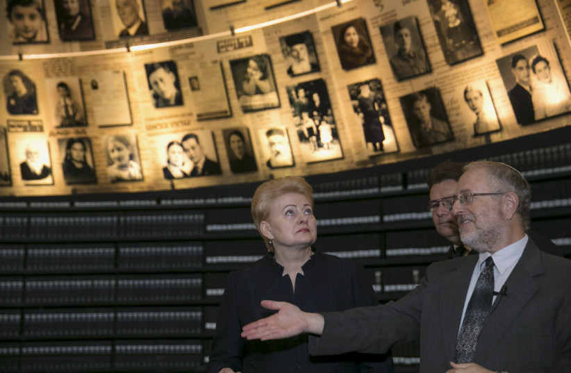 Former Lithuanian President Dalia Grybauskaite stands under pictures of Jews killed in the Holocaust during a visit to Yad Vashem's Hall of Names in 2015 (photo credit: BAZ RATNER/REUTERS)