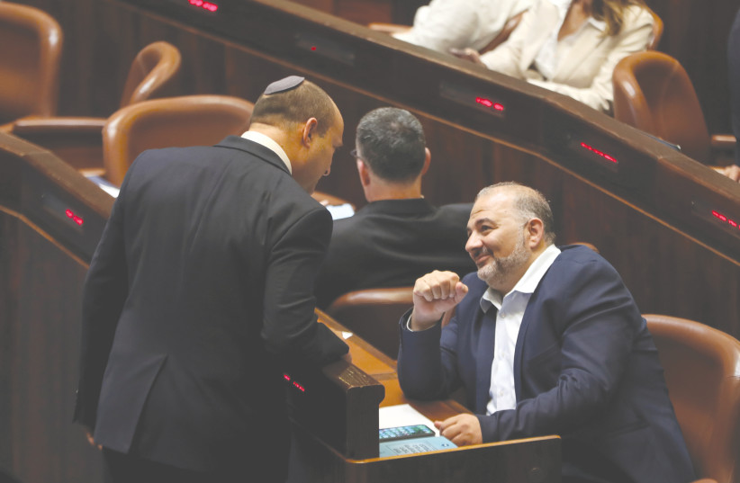 RIME MINISTER Naftali Bennett chats with United Arab List leader Mansour Abbas during a special session of the Knesset to swear in the new coalition government, in Jerusalem on Tuesday.  (credit: RONEN ZVULUN / REUTERS)