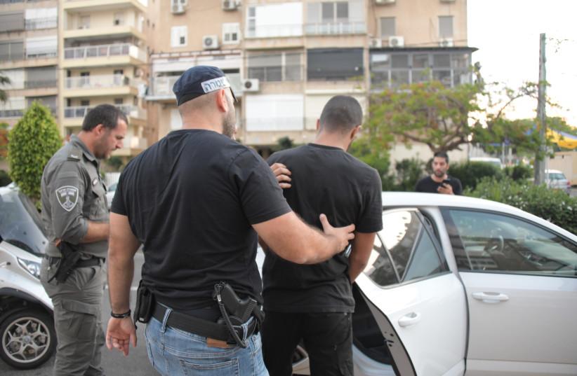 Israeli police officer arrests a man. (credit: ISRAEL POLICE)