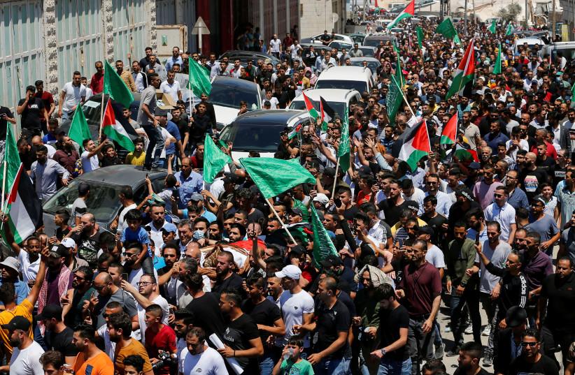 Des personnes assistent aux funérailles du critique palestinien Nizar Banat, décédé après avoir été arrêté par les forces de sécurité de l'Autorité palestinienne, à Hébron (crédit : MUSSA QAWASMA/REUTERS)