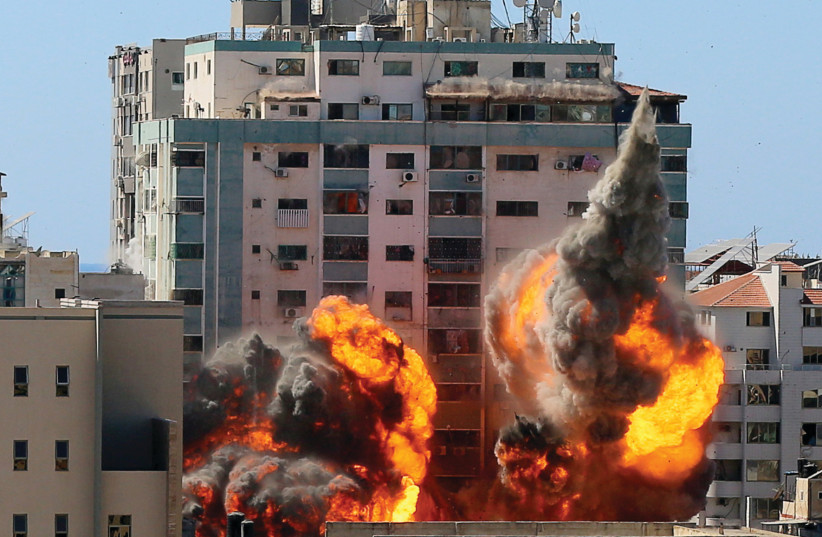 An explosion is seen near al-Jalaa Tower housing AP and Al Jazeera offices during Israeli missile strikes in Gaza City on May 15 (credit: ASHRAF ABU AMRAH / REUTERS)