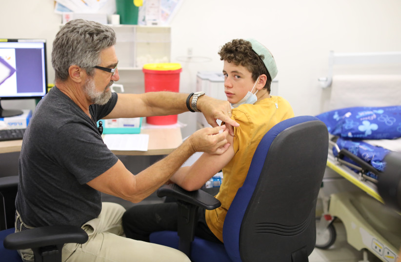 A boy receives a dose of the Pfizer-BioNTech vaccine at Jerusalem's Misgav Ladach Hospital on June 6, as Israel began its coronavirus vaccination campaign for 12-to-15 year olds (photo credit: MARC ISRAEL SELLEM)