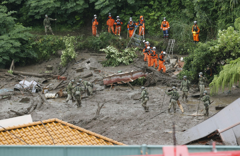 Members of Japanese Self-Defence Forces and firefighters conduct search and rescue operation at a mudslide site caused by heavy rain at Izusan district in Atami, west of Tokyo, Japan July 4, 2021. (photo credit: KYODO/VIA REUTERS)