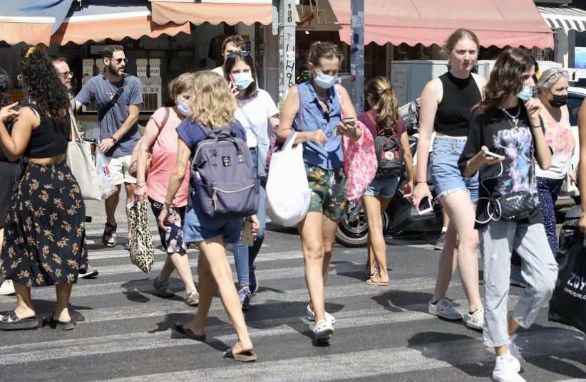Israelis walk the streets of Tel Aviv, July 6, 2021. (photo credit: MARC ISRAEL SELLEM)