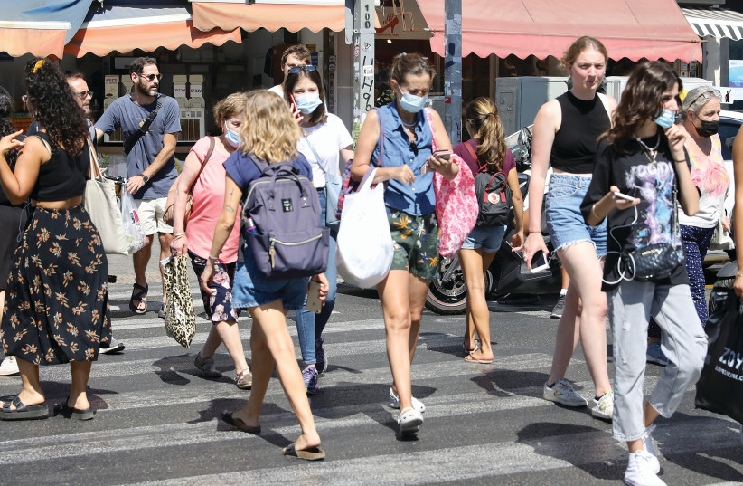 A TEL AVIV crosswalk this week, with a mix of masked and unmasked pedestrians. (credit: MARC ISRAEL SELLEM/THE JERUSALEM POST)