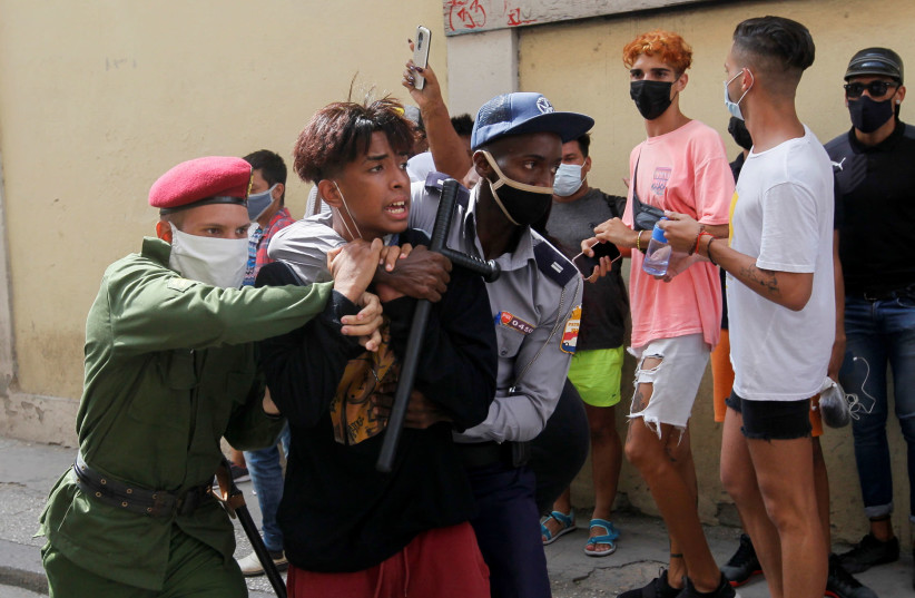Police detain a person during protests against and in support of the government, amidst the coronavirus disease (COVID-19) outbreak, in Havana, Cuba July 11, 2021 (photo credit: REUTERS/STRINGER)