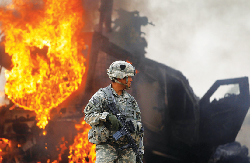 A US ARMY officer stands near a burning vehicle north of Kandahar, Afghanistan. (photo credit: BOB STRONG / REUTERS)