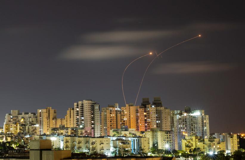 Des traînées de lumière sont visibles depuis Ashkelon alors que le système anti-missile Iron Dome intercepte des roquettes lancées depuis la bande de Gaza le 20 mai 2021. (Crédit photo : AMIR COHEN/REUTERS)